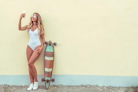 Beautiful blonde girl with long hair standing yellow wall in summer city. White body swimsuit board longboard. Free space for text. Selfie photo online call, social networks online, happy smiling. Banque d'images