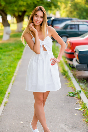 Young and beautiful girl posing in summer outdoors in a city park. Happy smiling in a white dress, tanned skin and long hair. Walk on track after work. Banque d'images