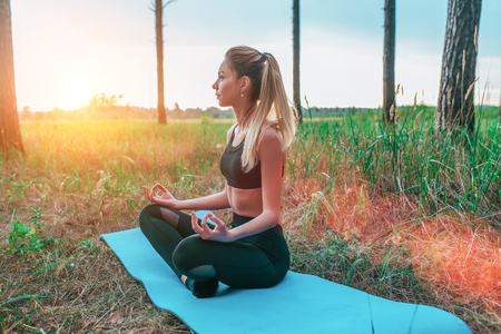 Beautiful girl sitting in the summer in the park. On a sports mat in the lotus position, meditates calm and balance of mind. Yoga on the nature of the soul, sports lifestyle in the forest. 写真素材