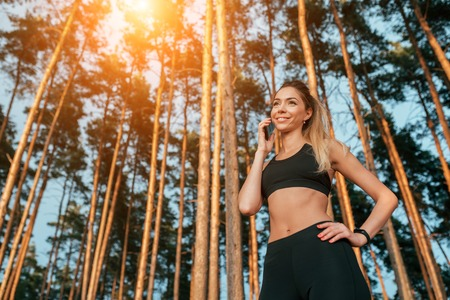 Beautiful girl standing in a summer forest park. Phone calls happy smiling. In sportswear jogging in the morning. Free space for text. Camping is a sport. 写真素材