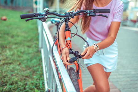 Password selection for protection. Girl locks bike parking lot. Concept of protecting property thieves, selection cipher code. lock with cipher metal cable theft bicycle. Summer city bicycle walk. Banco de Imagens