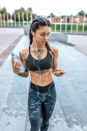 Young athletic beautiful girl in cat tattoos, morning fitness, headphones listens music on phone, online playlist app Internet, sportswear top leggings. Summer city workout. Bottle of water.