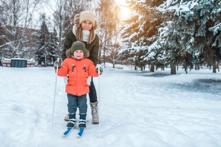 A young woman, mom supports with care, skiing in the winter in the forest park, a little son a boy of 3-6 years. The first sports lessons on the street. Caring for parent-child. Free space for text.
