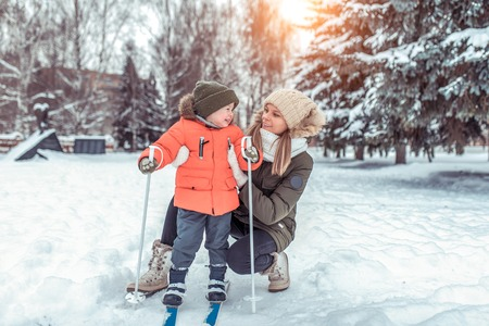 A young woman, mother supports with care, little boy son 4-5 years old, skiing winter in forest park. The first sports lessons on street. Happy smiling playing with child. Free space for text.