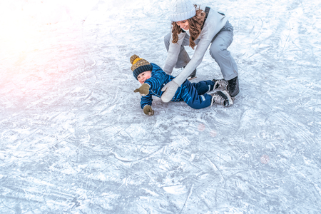 The baby fell on the ice. A young mother skates in the park in winter, with her son a young child 2-4 years old. Weekend rest at a public skating rink, happy smiling.