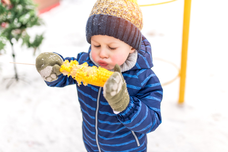 A small boy of 2-3 years old eats boiled corn on the street in the winter, against the background of snow in a warm jacket and hat, blowing on hot corn, trying to cool breakfast or snack in nature. Stockfoto - 119011180