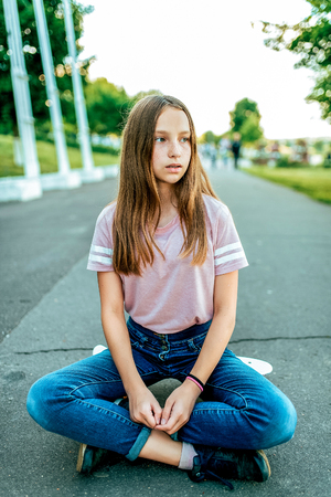 A little girl schoolgirl of 13-15 years old, on street sits skateboard in summer in park. Resting after walking and skating on board. Sits in lotus position, jeans and casual clothes in a T-shirt. Stockfoto