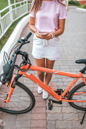 A girl holds a phone in her hands, takes pictures of a bicycle parking place, an online application to the Internet, and searches for a route around the city in the summer on a bicycle.