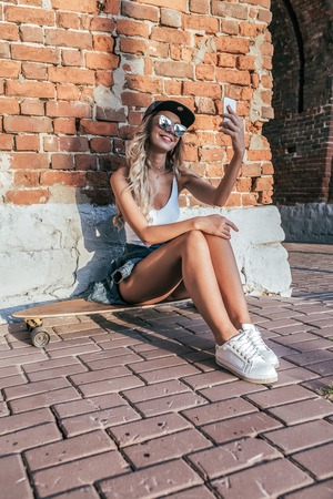 Beautiful happy girl sitting skateboard, longboard. He holding smartphone his hand, talking video call online application Internet. Taking pictures yourself makes selfie. In summer city has rest. Stock Photo