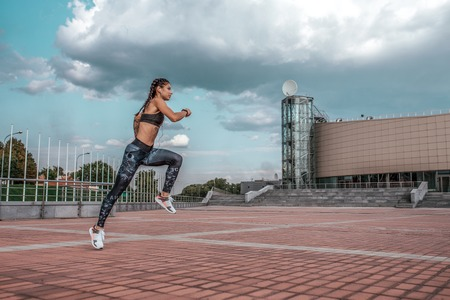 Beautiful jumping girl froze air. Active lifestyle, jogging and running city summer fresh air. Concept of strength, endurance, slim figure. Sport muscles in motion. Free space for text motivation.