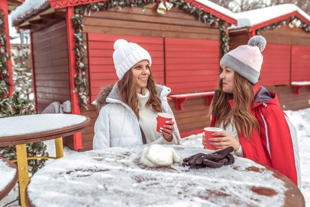 Two girls girlfriends talk in the winter at the table, holding cups of coffee tea, hot drink, breakfast, lunch, snack, in the open air. Emotions joy fun weekend at the resort. Stock Photo