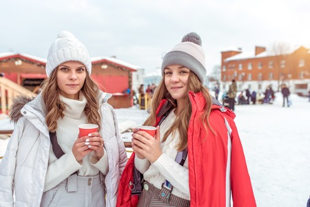 Beautiful women, two girls girlfriends posing in the winter, holding cups of coffee tea, hot drink, breakfast, lunch, snack, in the open air. Emotions joy fun weekend at the resort.