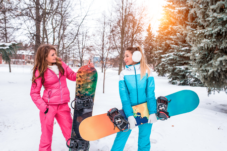 Two girls athletes, resting on a winter jacket, ski slope. Against the backdrop of snow trees and snow-covered fir trees. Happy talking in the hands of snowboards. Holiday resort at weekend.