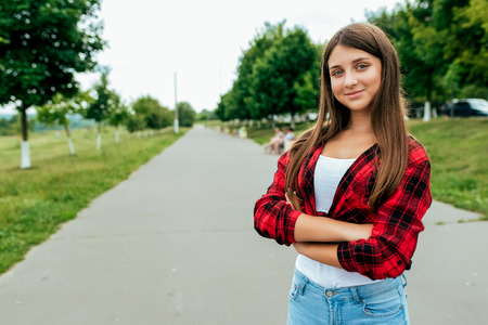 Happy girl teenager 12-15 years old schoolgirl, stands road. In summer in city after school. Holiday weekend city. Red shirt T-shirt and jeans. Free space for text. Emotions of joy, fun, lifestyle.