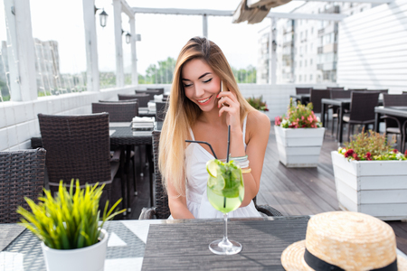 Joyful girl calls on the phone, summer cafe, fresh air on the veranda. Woman white dress cocktail glass. Long hair tanned skin. Emotions of joy of happiness talking and pleasure.