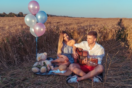 Young couple man woman summer wheat field rug. They play guitar singing songs. Joyful fun laugh. Romantic love, date holiday anniversary wedding anniversary. Emotions tenderness care celebration.