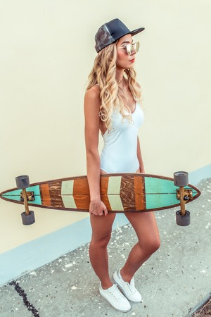 Beautiful girl in a white bodysuit baseball cap and sneakers, holding a longboard skateboard in her hands. Summer resting, fashionable lifestyle, fashion young. Concept idea of an active lifestyle. Foto de archivo