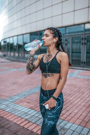 Beautiful girl athlete, summer city with tattoo of a cat, drinking water from a bottle. In his hand, phone listens to music on headphones. Rest after training. Motivation sports. Active lifestyle.