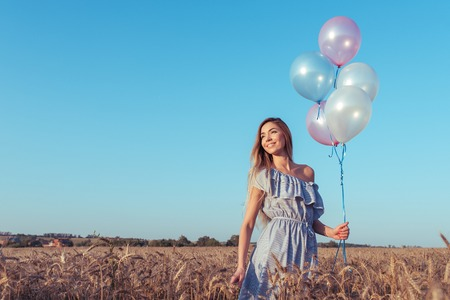 Beautiful and young girl holding balloons her hands, summer wheat field. Blue dress and long hair, tanned skin. Emotions joy fun, gift and a holiday in the out door in nature. Free space for text.