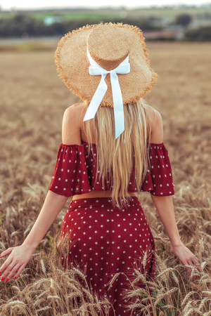Girl wheat field summer red dress straw hat. View from rear, walk summer across field, outdoor recreation village. Concept of freedom thought. Long hair, tanned skin. Slim figure of a woman.