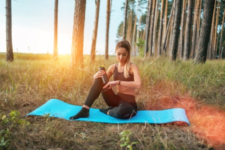 Beautiful girl engaged in sports yoga on mat. In summer forest, park. In hand a shaker with water and protein. Looks smart bracelet watches. Check pulse workout. The concept of healthy lifestyle.