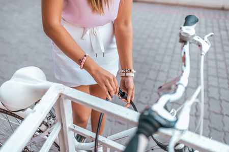 Close-up, girl summer city. Locks your bike. Picks up password lock. Parking installation of cable and lock with code. Concept against theft and theft of bicycle. Lock lock to fence and fence. Stockfoto