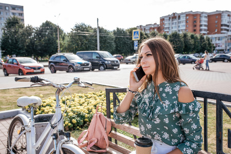 Beautiful girl sitting on bench, bike and bag. In summer on fresh air. Lifestyle in city. Calls on phone, in his hand a cup of coffee. The concept of online communication in social networks.