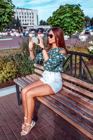 A brunette girl sits in the summer on a bench. In the hands of the phone, makes photos on the smartphone. Happy smiling in sunglasses, green blouse and white skirt shorts.