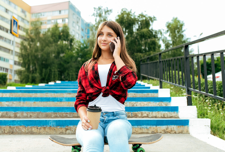 A schoolboy girl in the summer in the park sits on a skateboard. Calls to parents and girlfriends. Happy smiles. Online application to intrentt. Long hair mug with tea. Stock Photo