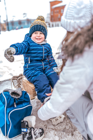 Young mother puts skates in winter public skating rink. The little boy happy smiling shows his hand to the side, in blue jumpsuit, mittens in snow. Learning ice skating in the winter on ice.
