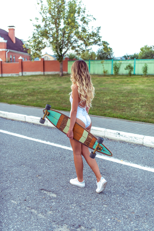 A beautiful tanned girl in white swimsuit bodysuit, in summer in city goes on road. Long hair tanned skin. Concept of fashion style and outdoor recreation. In the hand of a skateboard, longboard.