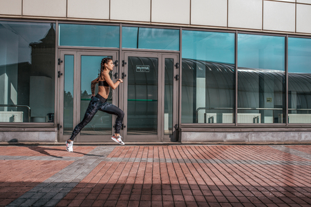 A beautiful woman, a girl runs in the summer in the city, on a morning jog, tanned skin. Sportswear leggings top. Phone earphones. Fitness concept jogging, lifestyle. Free space for text.