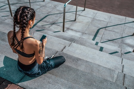 Woman athlete in tattoos, in summer city, resting after workout fitness, workout. Sportswear leggings top. Headphones smartphone. Online application social networks. Listening to music. Free space. Stockfoto