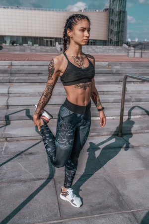 Girl athlete in tattoos, in summer in city, trains fitness, gymnastics workout. Sportswear leggings top. In the morning before run. Background steps. It warms the muscles before exercise. Stok Fotoğraf