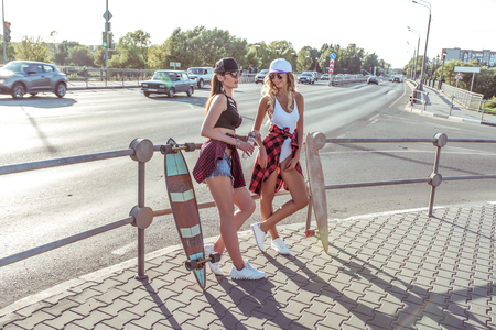 Two girlfriends, beautiful girls stand summer city, background road, crossroads. People talking smiling. Skateboard, longboard. Tanned skin has long hair. Concept fashion lifestyle young people. Imagens