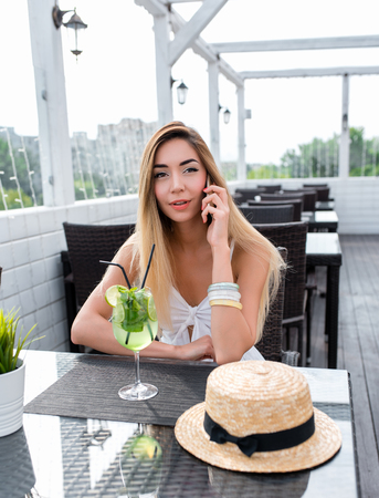 Beautiful woman restaurant dress, girl summer cafe. Calls mobile phone. On table, cocktail hat. Long hair everyday makeup. Rest after work. Conversation concept online via internet application.