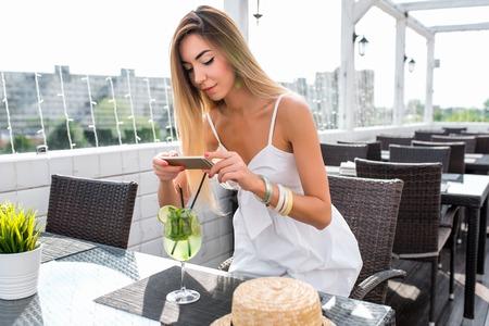 Schönes Frauenrestaurantkleid, Mädchensommercafé. Fotografien Cocktail auf Tisch, Hut. Alltags-Make-up für lange Haare. Ruhen Sie sich nach der Arbeit aus. Konzept von sozialen Fotonetzwerken, Videoaufzeichnungs-Smartphone. Standard-Bild