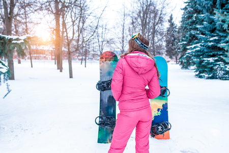 The girl in the winter on the background of snow and snowboards, green spruce. Stands back in a pink warm sports jumpsuit. It is worth waiting for friends at the resort. Free space for text. Imagens