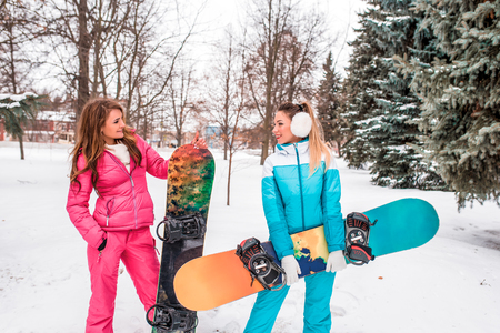 Two girlfriends girl in winter background of snow and fir trees, hold snowboards, skating boards in their hands. Happy women are smiling, talking, relaxing resort on weekends holidays. Stok Fotoğraf