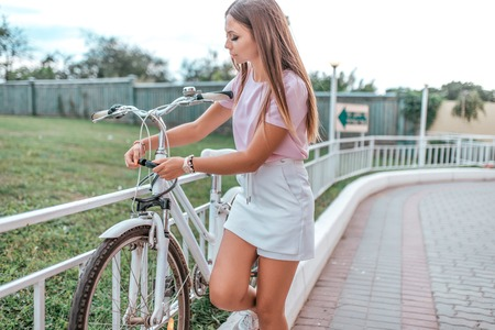 Girl in summer stands at bike, locks bike with cable. Picks up a password on the lock, against theft of a bicycle in parking lot. Bicycle rentals Cycling on the weekend. Active lifestyle. Stockfoto