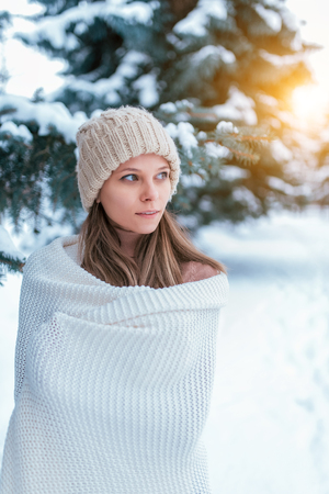 A woman in a white plaid, in the winter on the street, background snow drifts Christmas tree. Happy smiles. The concept of outdoor recreation on weekends, holidays at the resort. Warm hat long hair.