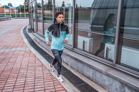 Woman athlete girl runs in the city in autumn in the spring, fitness workout, motivation is power. Active lifestyle. Sportswear, free space, achievement, success, endurance competition. 版權商用圖片