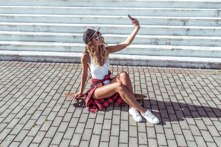 Woman summer city white body. Skate board Beautiful slim figure, sunglasses sneakers. Photographs phone online video call application happy smiling. Concept fashion style modern lifestyle. Free space