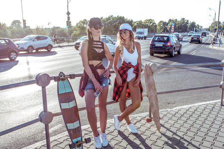 Two girlfriends girl intersection road, background cars transport bridge, walk summer city, skate board, casual wear shorts swimsuit shirt. Concept weekend getaway, fashion style, modern lifestyle. Imagens