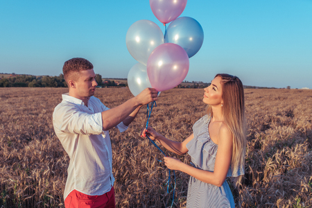 Young couple man woman summer wheat field with balloons. Concept romance bye love, birthday engagement party, caring family support honeymoon. Emotions joy smiles, pleasure outdoor recreation