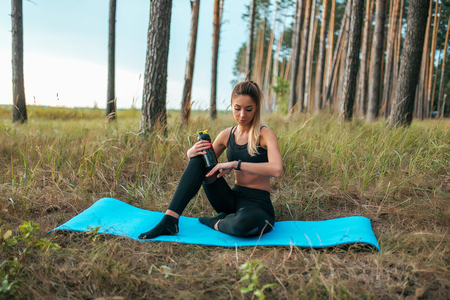 Woman mat summer forest, gymnastics concentrates practicing yoga. Looks watch smart bracelet, heartbeat pulse, time. Counting calories workout. In hand, shaker with water drink gainer protein