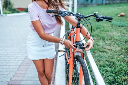 Woman summer city bicycle parking. Blocks metal cable bicycle. Protection property from theft concept anti-theft lock with cipher, password selection with code Locks cable with numeric code lock.