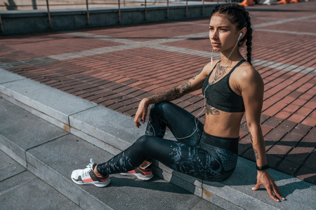 Woman athlete resting after summer workout city. Headphones phone online application music social networks. Concept fitness fresh air active lifestyle workout. Tattoos tanned figure. Free space text