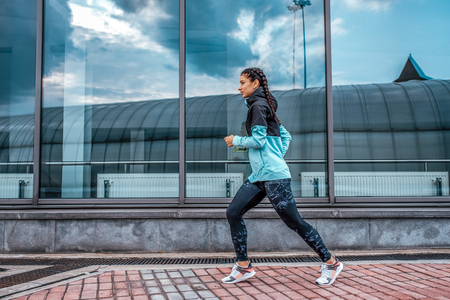 Athlete girl running sports jogging training summer city. Concept fitness fresh air, active lifestyle workout. Free space. In morning evening motivation strength spirit, sportswear jacket leggings