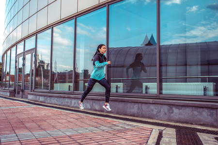 Woman sports trainer, summer city, run jump, fitness workout. Motivation strength mind thoughts. Beautiful girl morning run. Free space. In morning, spirit, sportswear jacket leggings sneakers